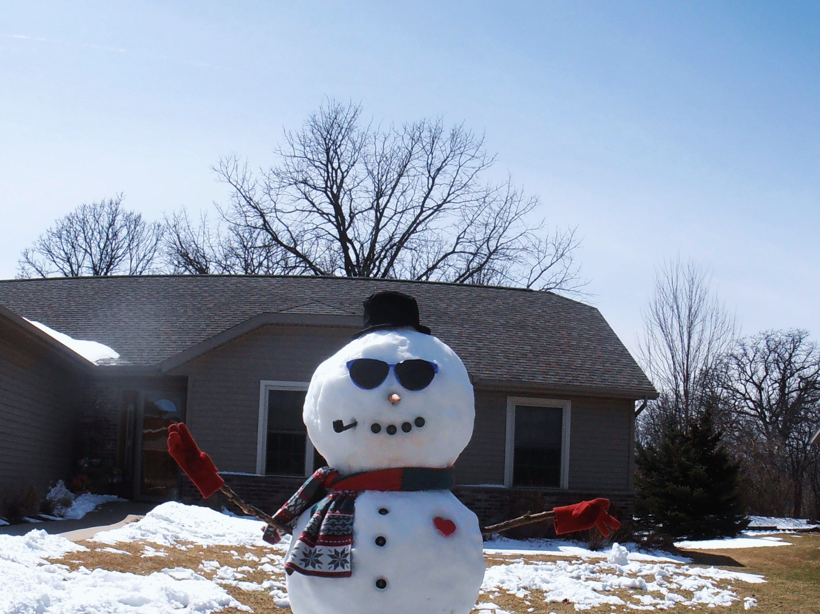 A snowman from a previous year decked out in sunglasses and mittens.