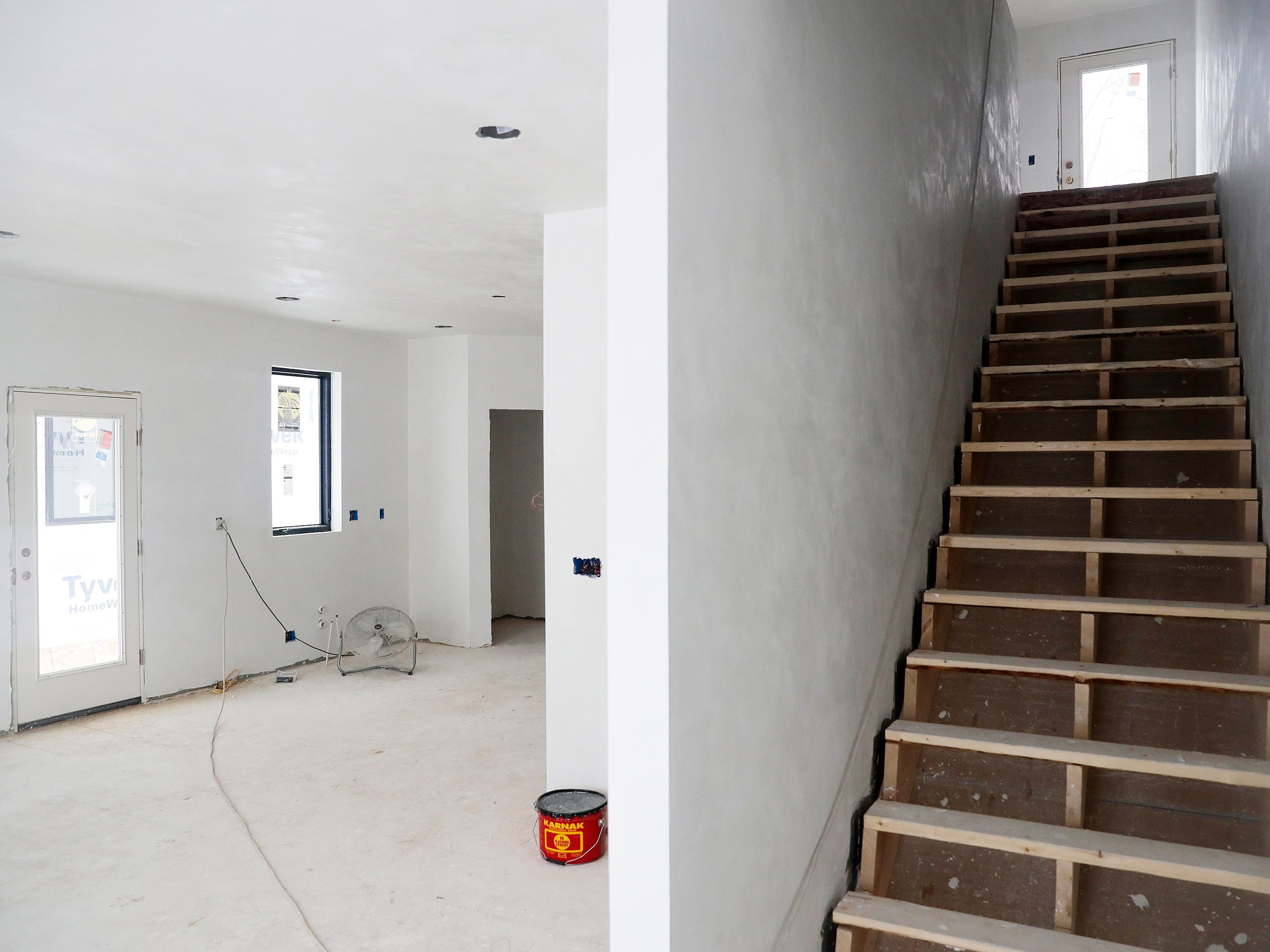 The living room is shown from the entryway of one of the under-construction townhouses on the corner of Van Buren and Cherry streets on Tuesday, February 26, 2019 in Green Bay, Wis.
