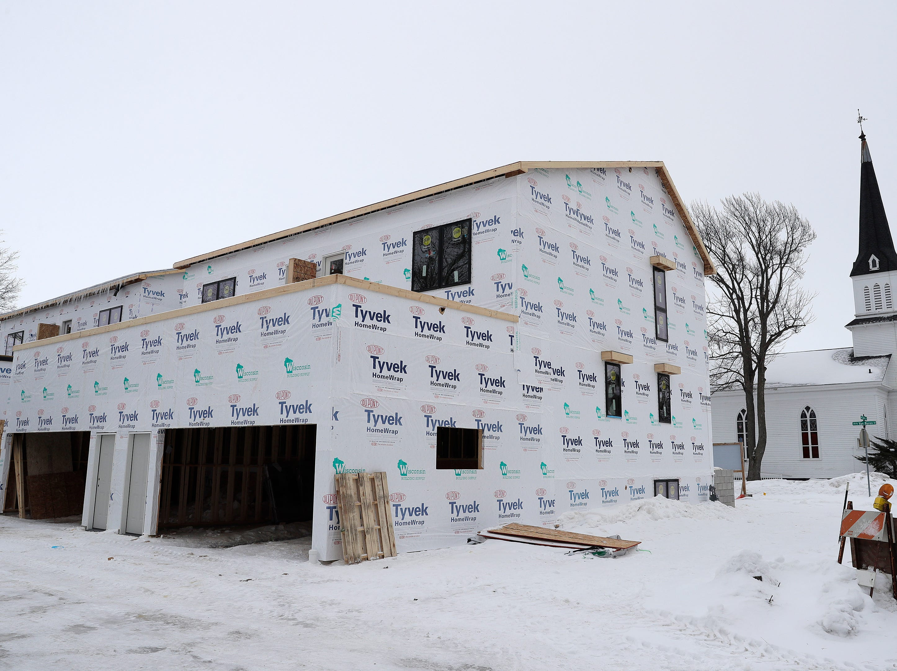 Under-construction townhouses on the corner of Van Buren and Cherry streets are shown on Tuesday, February 26, 2019 in Green Bay, Wis.