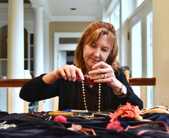 Lauren Demosthenes makes jewelry at her home in Greenville.
