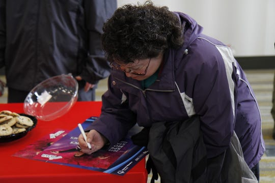 Denise Almanza signing a poster for an attendee of the press conference.