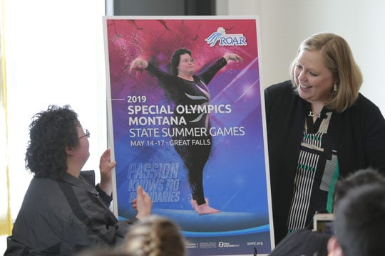 Denis Almanza happily points at herself in the official 2019 poster after unveiling it with Jamie Wood.