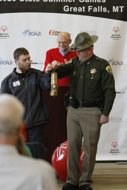 Great Falls Athlete Jared Redeen and Montana Highway Patrol Trooper Jim Humiston presenting the Flame of Hope in a miner's lantern.