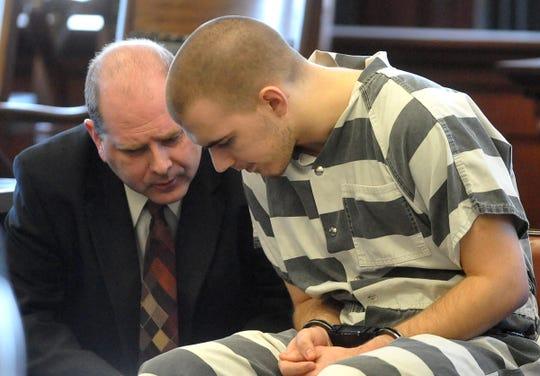 Matthew McKittrick talks with client Bradley Crisman during a change of plea hearing in 2012.