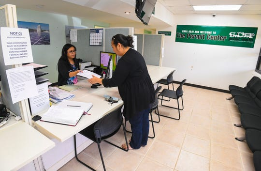 Customer Emily Cruz, right, is assisted by Lea Sanchez, Department of Public Works customer service representative, at the Permit Center at the DPW compound in Tamuning on Tuesday, Feb. 26, 2019.