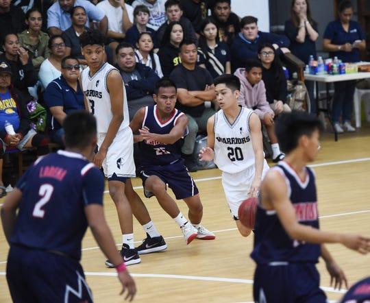 Saint Paul's Brandon Miranda (20) handles the ball against the Okkodo Bulldogs during a IIAAG Boys' Basketball game at the Saint Paul Christian School Gym, Feb. 26, 2019. The Warriors won the game 64-50.