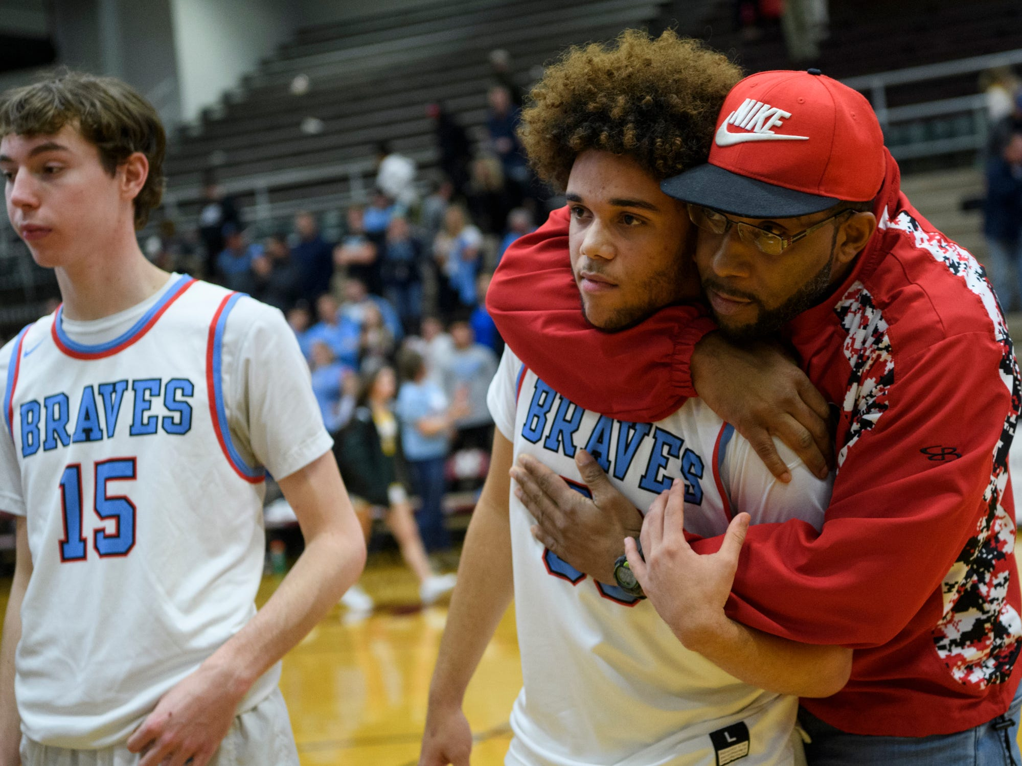 Union County's Dreyton Davis (30) receives a hug as fans sing and cheer for them after a tough loss to the Caldwell County Tigers in the Boys Second Region tournament at Madisonville-North Hopkins High School in Madisonville, Ky., Monday, Feb. 25, 2019. The Tigers defeated the Braves 67-64 to advance to Friday's second region semifinal against University Heights Academy.