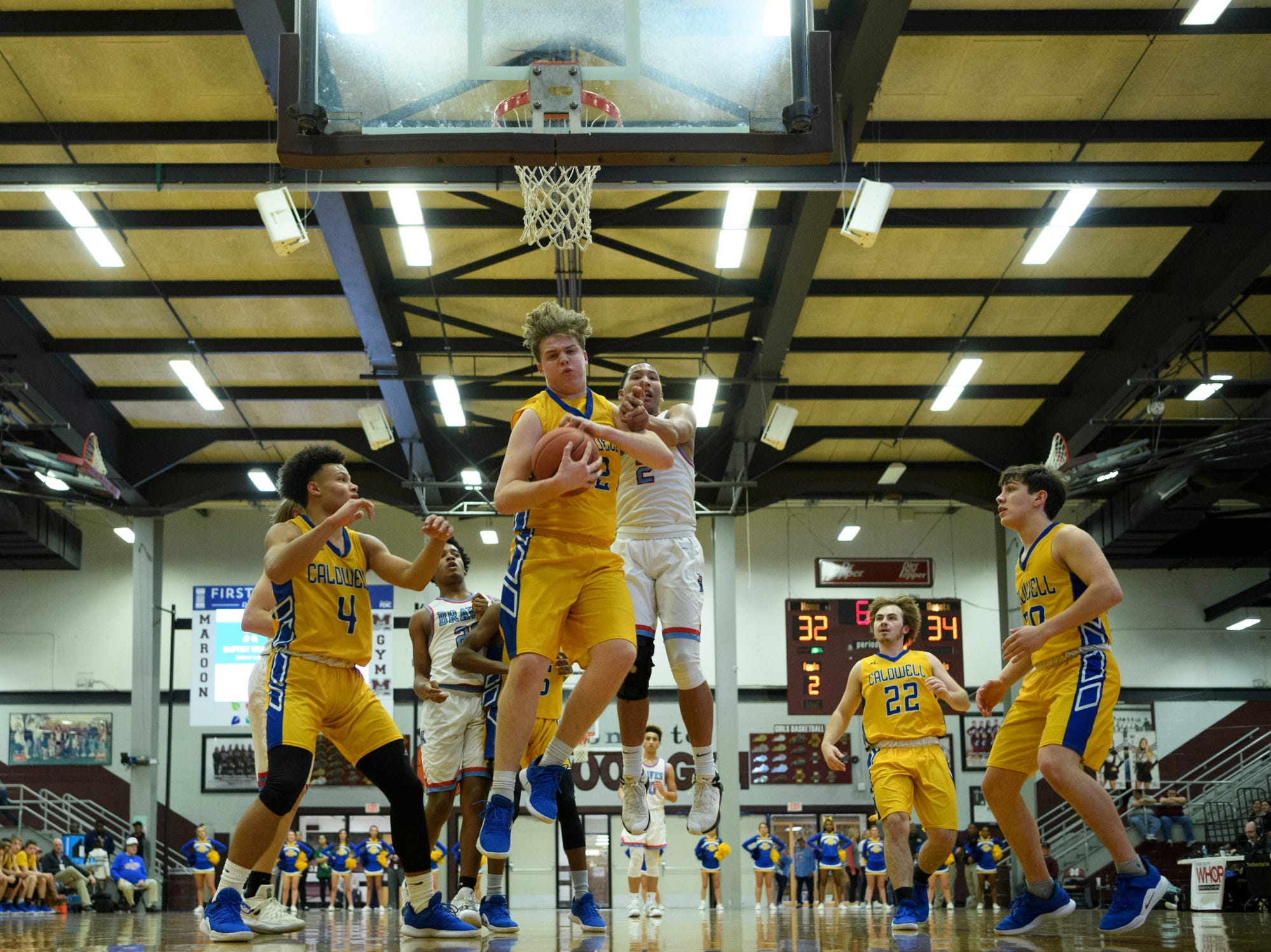 Caldwell County's Cole Smiley (42) and Union County's Kaleb Kanipe (2) fight for a rebound during the Boys Second Region tournament at Madisonville-North Hopkins High School in Madisonville, Ky., Monday, Feb. 25, 2019. The Tigers defeated the Braves 67-64 to advance to Friday's second region semifinal against University Heights Academy.