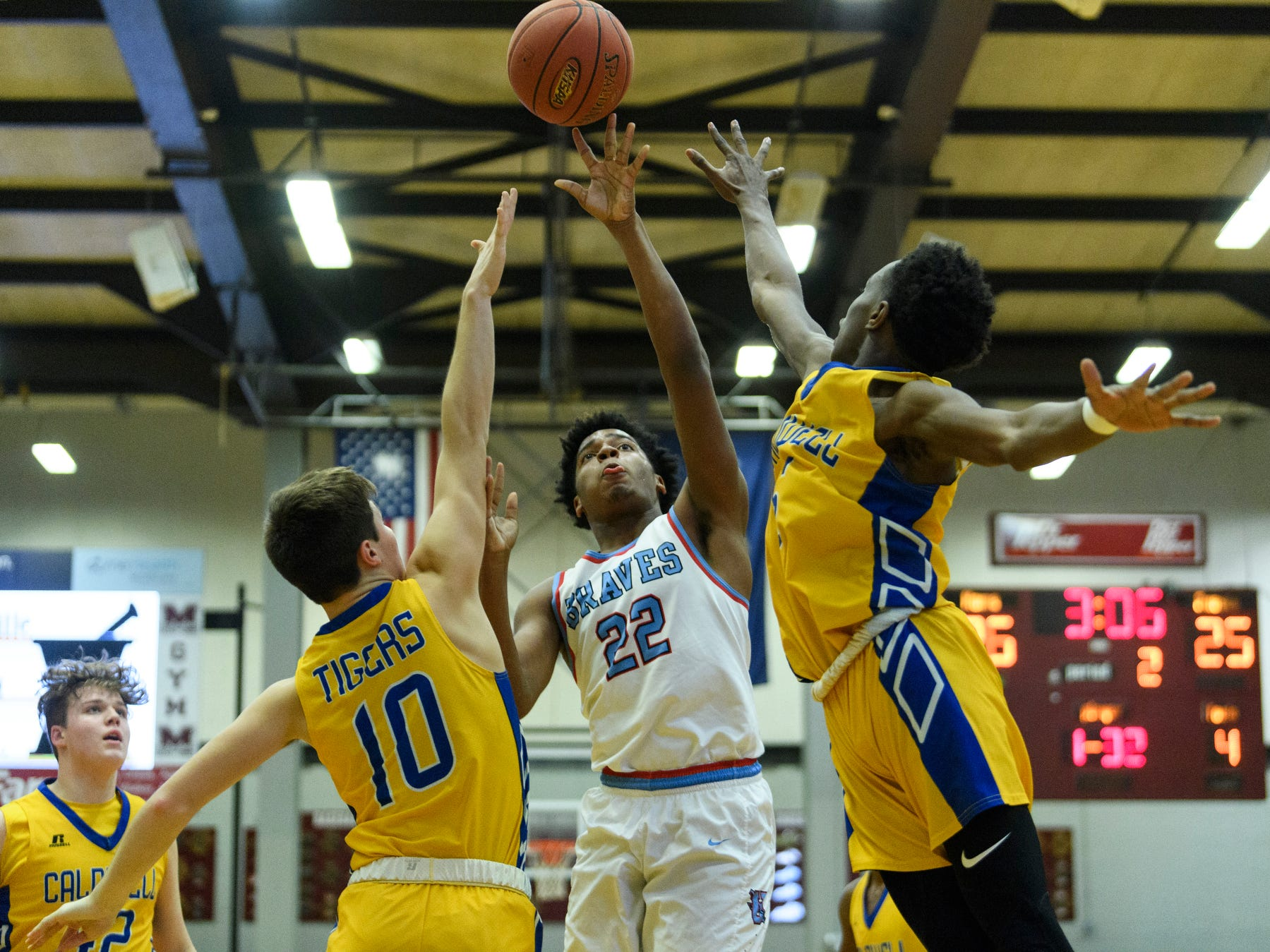 Union County's Iverson King (22) goes for the net as Caldwell County's Tripp Branch (10) and JaMarius D Blaine (5) attempt to block his shot during the Boys Second Region tournament at Madisonville-North Hopkins High School in Madisonville, Ky., Monday, Feb. 25, 2019. The Tigers defeated the Braves 67-64 to advance to Friday's second region semifinal against University Heights Academy.