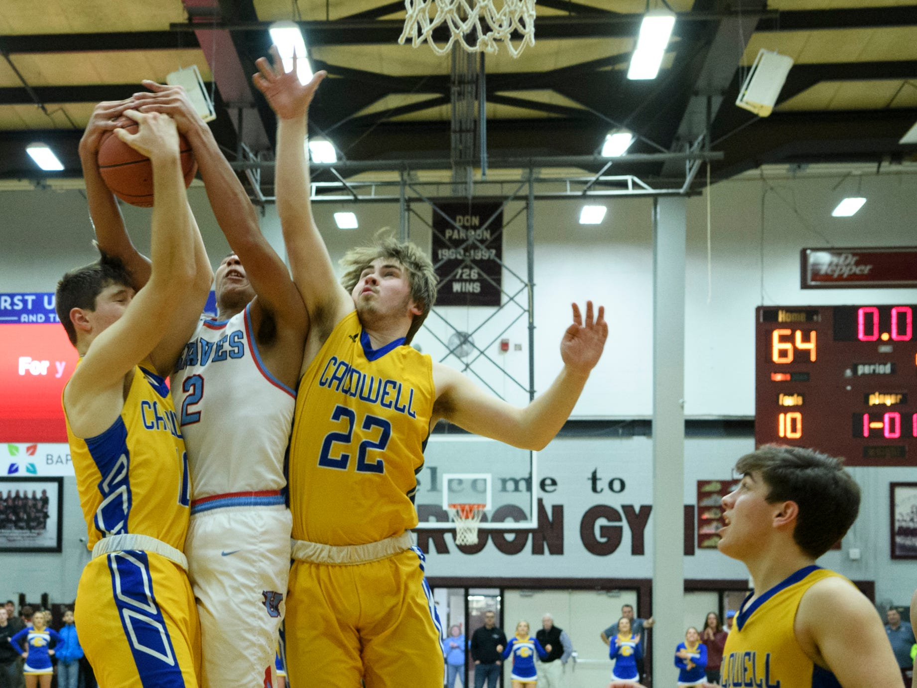 Caldwell County's Tripp Branch (10), Union County's Kaleb Kanipe (2) and Caldwell County's Cayden Fraliex (22) fight for a rebound during the Boys Second Region tournament at Madisonville-North Hopkins High School in Madisonville, Ky., Monday, Feb. 25, 2019. The Tigers defeated the Braves 67-64 to advance to Friday's second region semifinal against University Heights Academy.