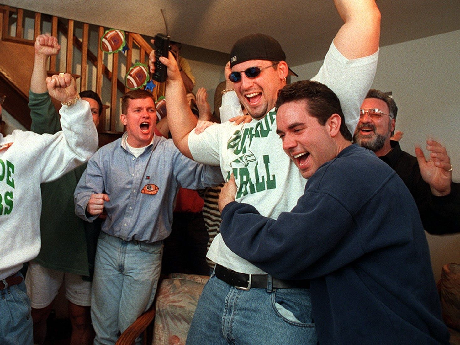 Ross Verba, phone in hand, celebrates with dozens of friends and family as news of his selection in the 1997 NFL Draft was announced on TV. Verba, a former Iowa Hawkeye, was taken 30th ovearll by the Green Bay Packers. He was hugged by his cousin, John Fucaloro. On his left is cousin Steve Fucaloro.