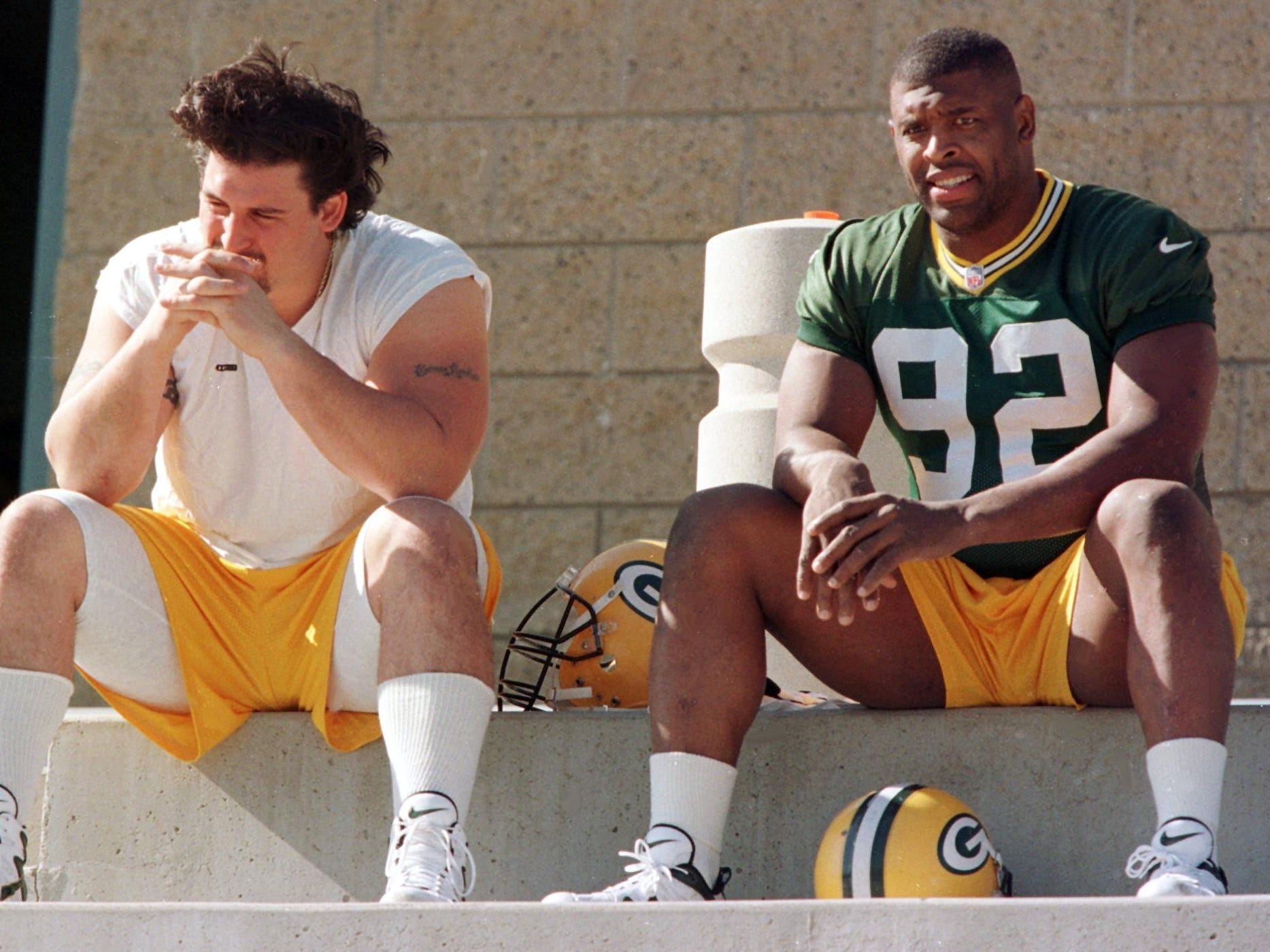 Green Bay offensive lineman Ross Verba, left, and defensive lineman Reggie White wait for practice before Super Bowl XXXII, where the defending champion Packers lost to the Denver Broncos.
