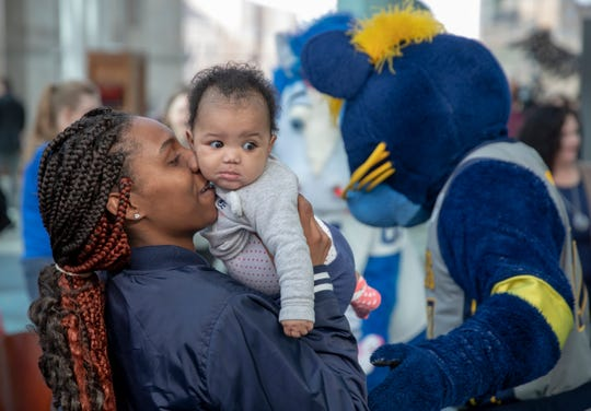 Tabitha Price, Indianapolis, holds her daughter Jamari Price, 6 mos., during an initiative called 'Next 50' which will seek to raise $150,000 in public donations to the Indianapolis Public Library, Tuesday, Feb. 26, 2019. Price had been at the library with her three children and stopped by to meet Pacers mascot Boomer.