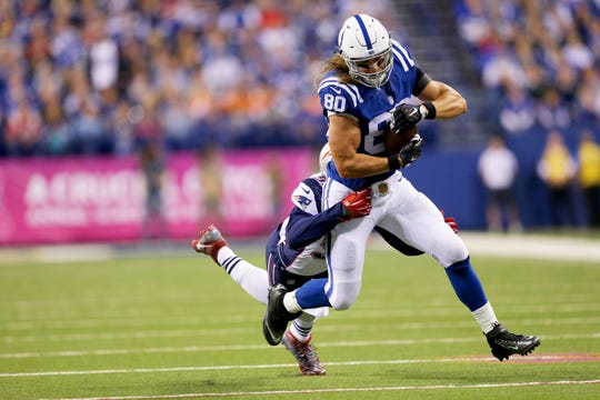 Indianapolis Colts tight end Coby Fleener (80) is hit by New England Patriots free safety Devin McCourty (32) as he advances the ball upfield during first half action of an NFL football game Sunday, Oct. 18, 2015, at Lucas Oil Stadium.