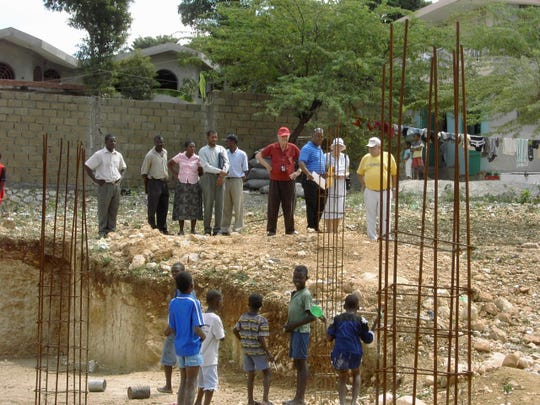 Don Miller, pictured in red, stood at a new church construction in Haiti during one of his mission trips in this undated photo.