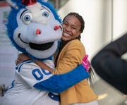 Blue, Colts mascot, gives a hug to Tamika Catchings, during a press conference for an initiative called 'Next 50' which will seek to raise $150,000 in public donations to the Indianapolis Public Library, Tuesday, Feb. 26, 2019. Children's reading and learning initiatives are the beneficiaries of the program that is being aided by mascots from the Indians, Colts, and Pacers.