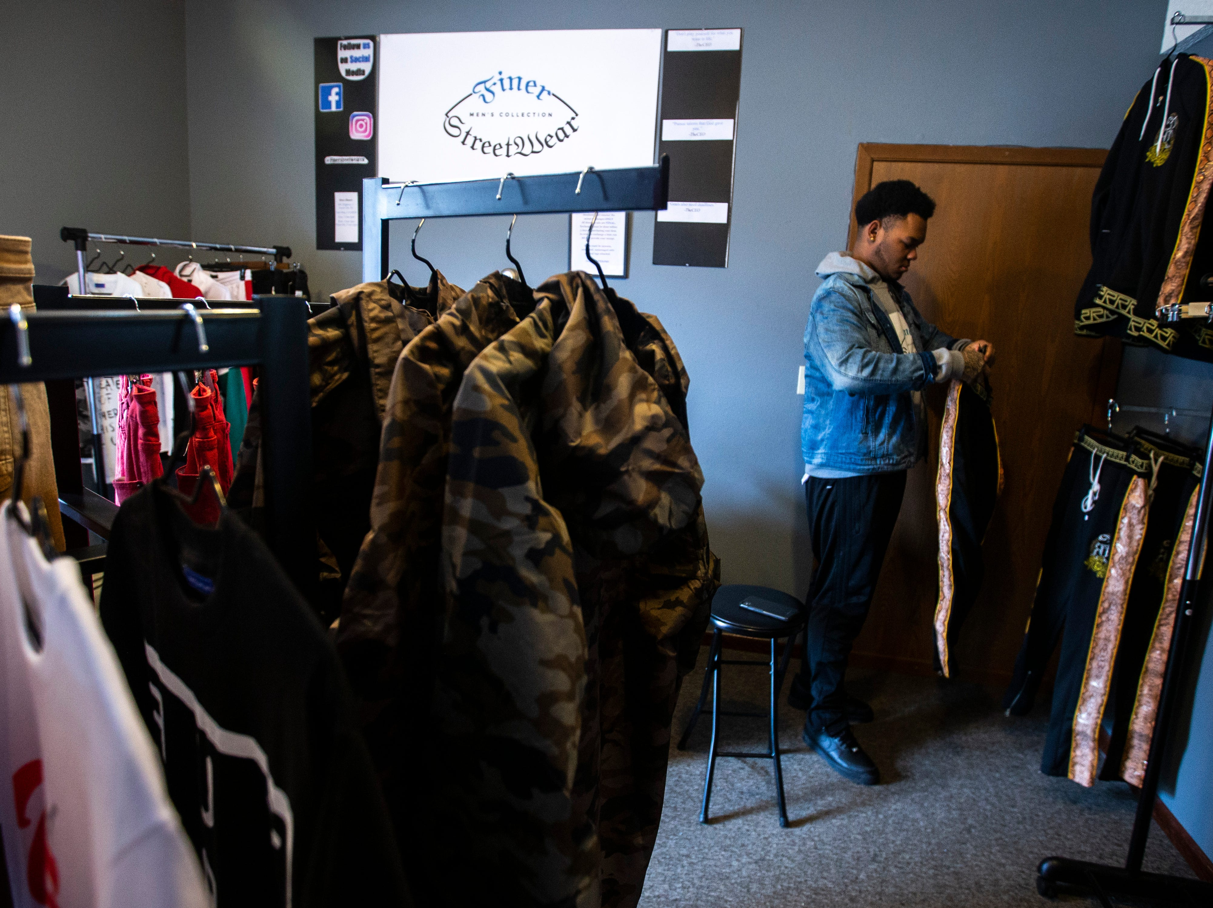 Markeece Johnson organizes inventory on Tuesday, Feb. 26, 2019, inside Finer Streetwear Co. at 441 Highway 1 West in Iowa City, Iowa. Johnson opened the store in November of 2018.