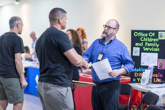 Todd Etchison, right, with the New York State Office of Children and Families, interacts with a job seeker at the 2018 Beyond the Box Reentry Job Fair in Ithaca.