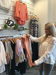 Mary Katherine Reynolds of Flowood, store manager at Highland Park by Material Girls in Ridgeland, checks merchandise.