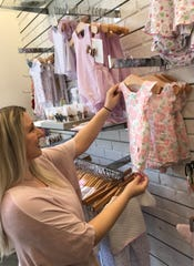 Sara Saxton of Yazoo City, a sales associate at Highland Park by Material Girls, straightens clothing for baby girls.