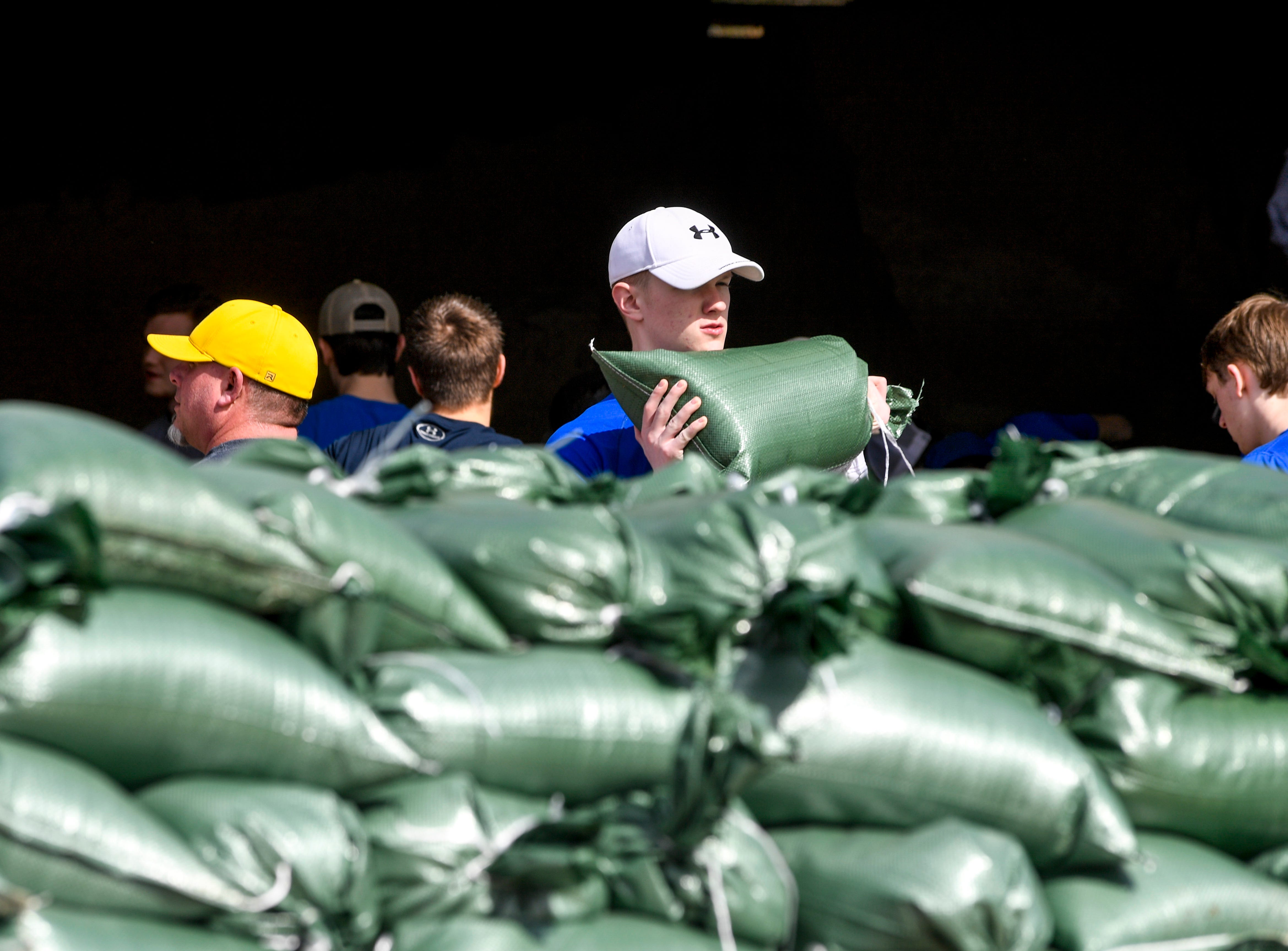Riverside High School football and baseball players filled sand bags for any residents to utilize and take at Decatur County Highway Department, in Decaturville, Tenn., on Monday, Feb. 25, 2019.