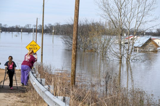 Residents pull over to jump out of the car and look at and take pictures of the damage caused by severe flooding at Tennessee River Bridge, in Savannah, Tenn., on Monday, Feb. 25, 2019.