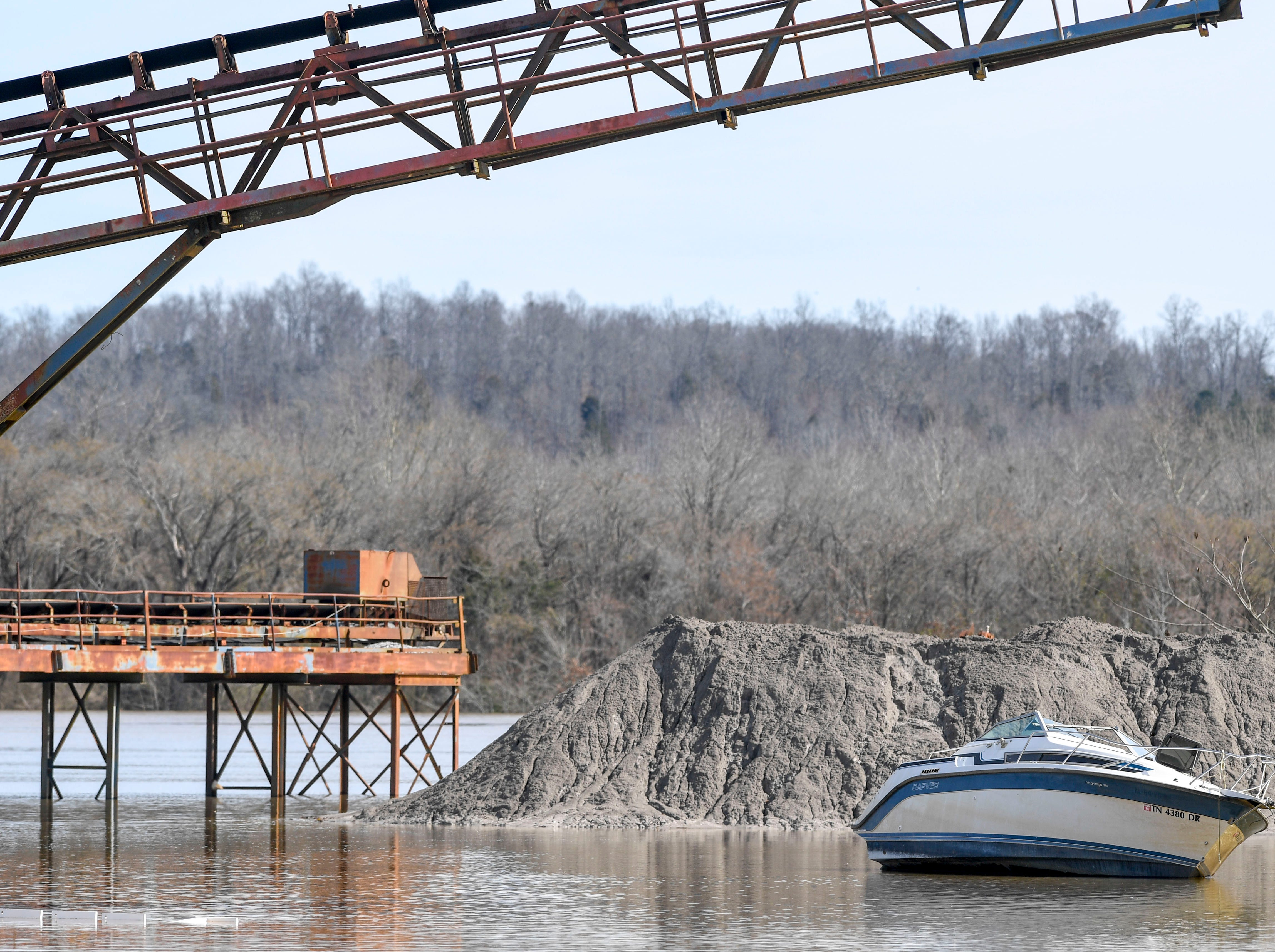 A boat having previously been beached on land in an old work yard touches water for the first time as floodwaters rise up from the Tennessee River at Hwy 100, in Decaturville, Tenn., on Monday, Feb. 25, 2019.
