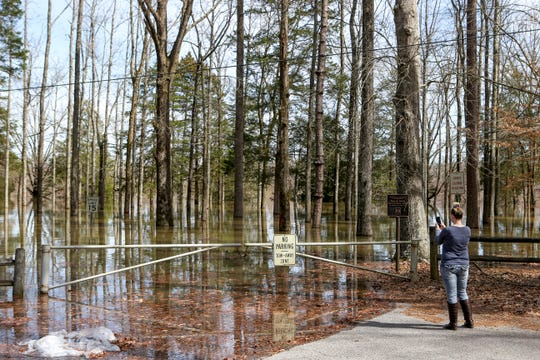 Belinda Conway snaps pictures of the flooding extent at Decatur County Beach Bend Park, in Decaturville, Tenn., on Monday, Feb. 25, 2019.