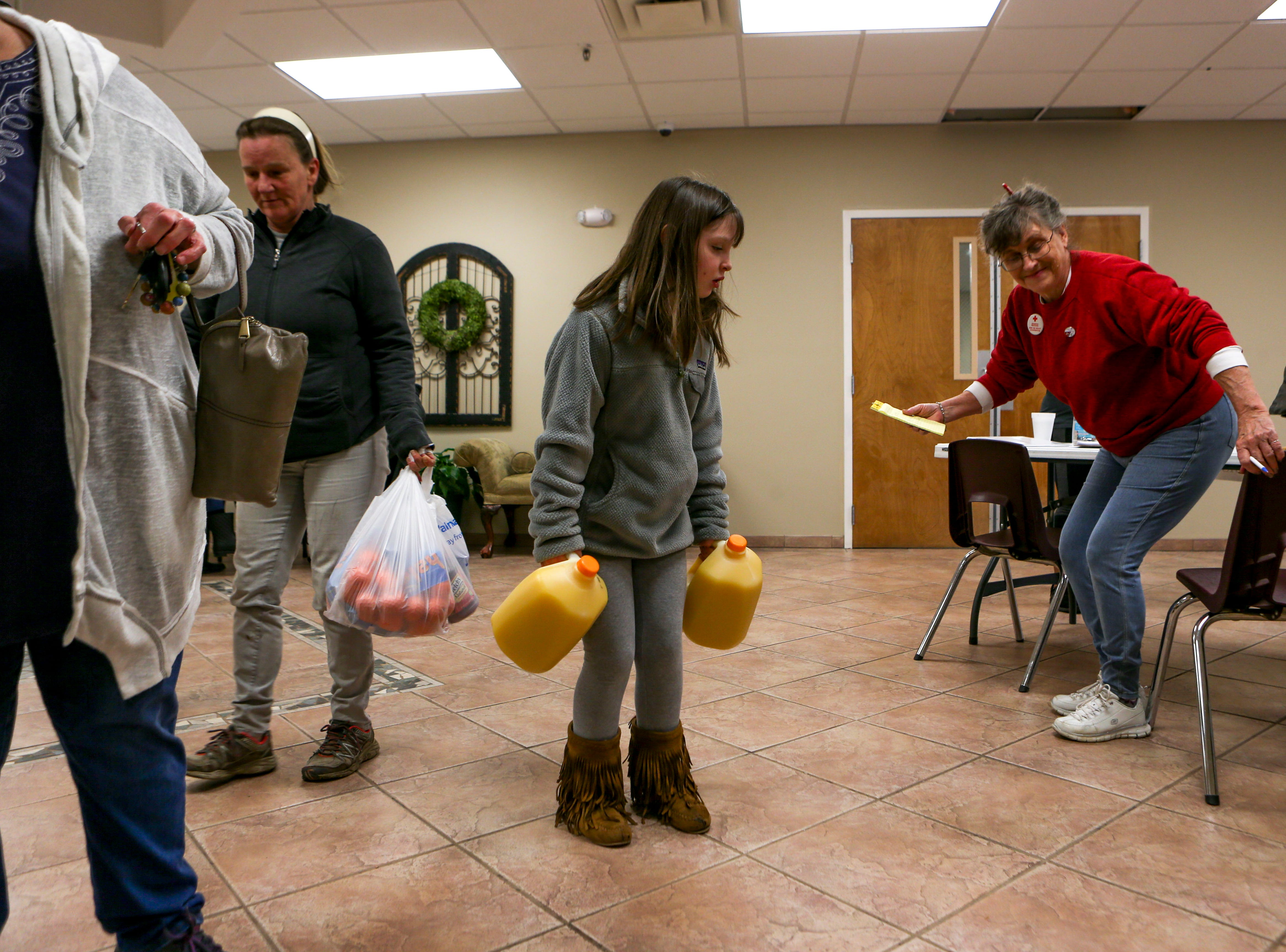 Natalie Seaton, 7, brings in jugs of orange juice to donate to The American Red Cross shelter established at Savannah Church of Christ, in Savannah, Tenn., on Monday, Feb. 25, 2019.