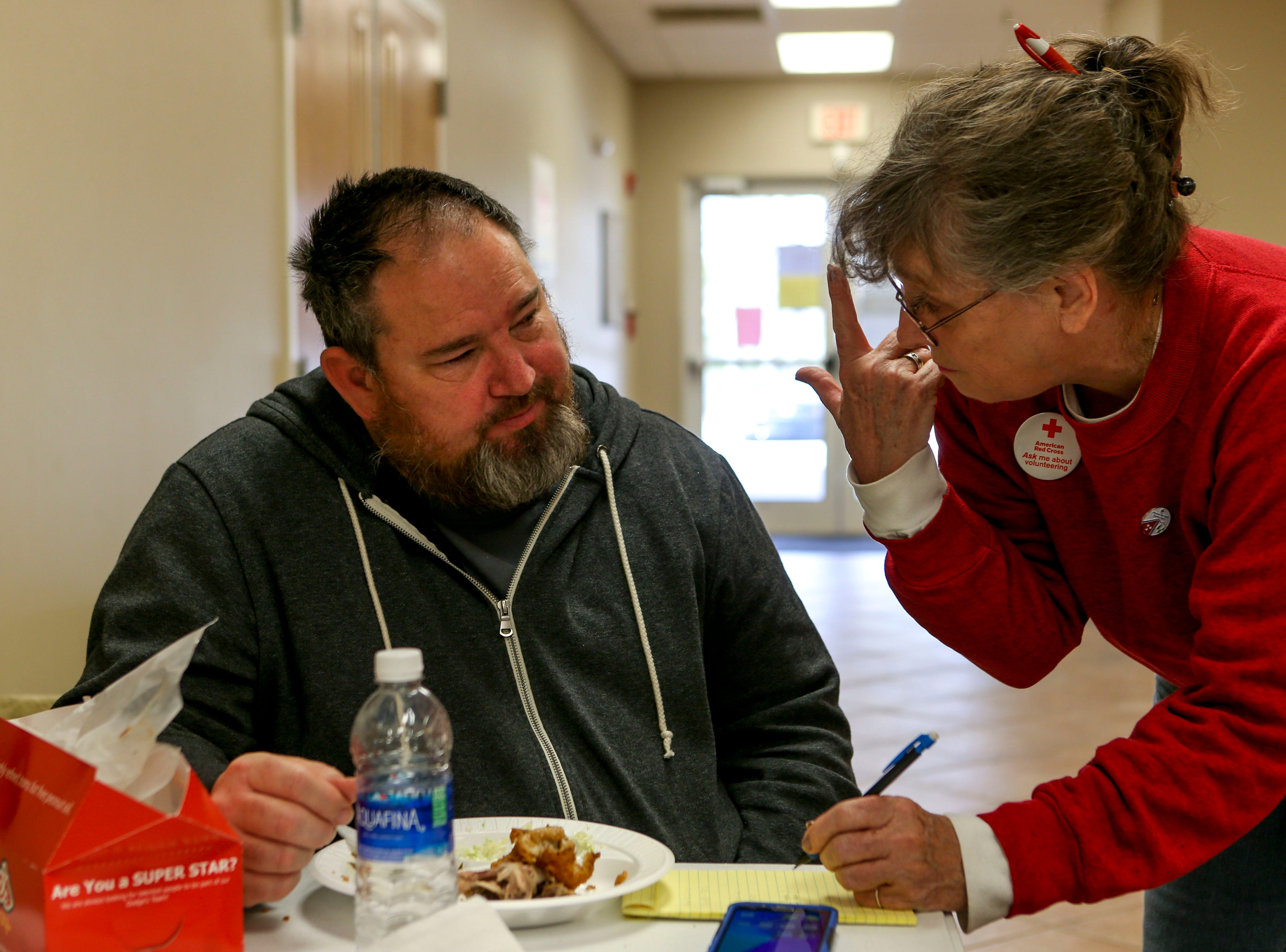Frank Taylor speaks with an American Red Cross volunteer Jackie while Jackie takes down notes for the glasses Taylor lost in the flood at Savannah Church of Christ, in Savannah, Tenn., on Monday, Feb. 25, 2019.