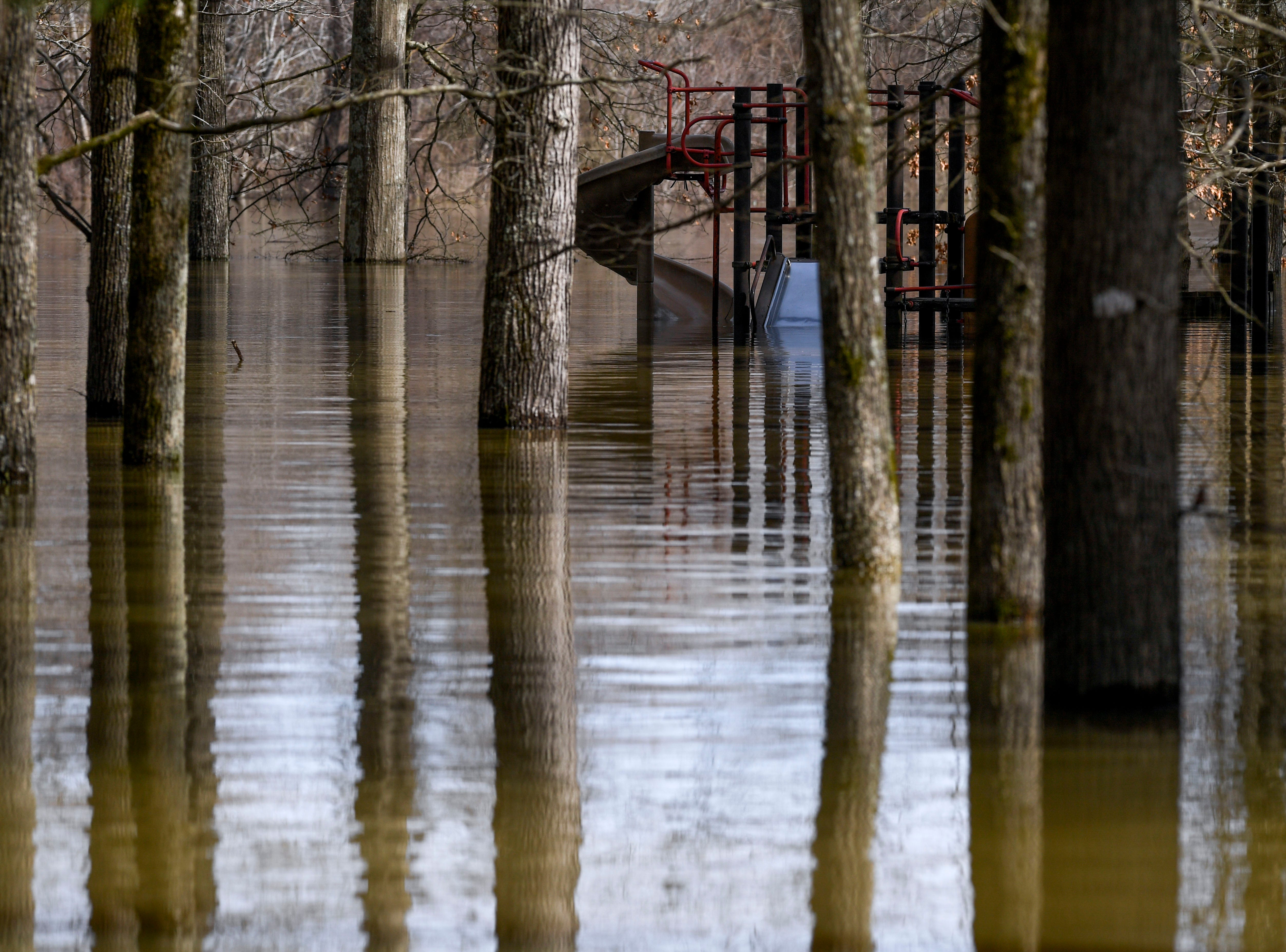 A slide can be seen in the distance and overcome by flood waters at Beech Bend Park, in Decaturville, Tenn., on Monday, Feb. 25, 2019.
