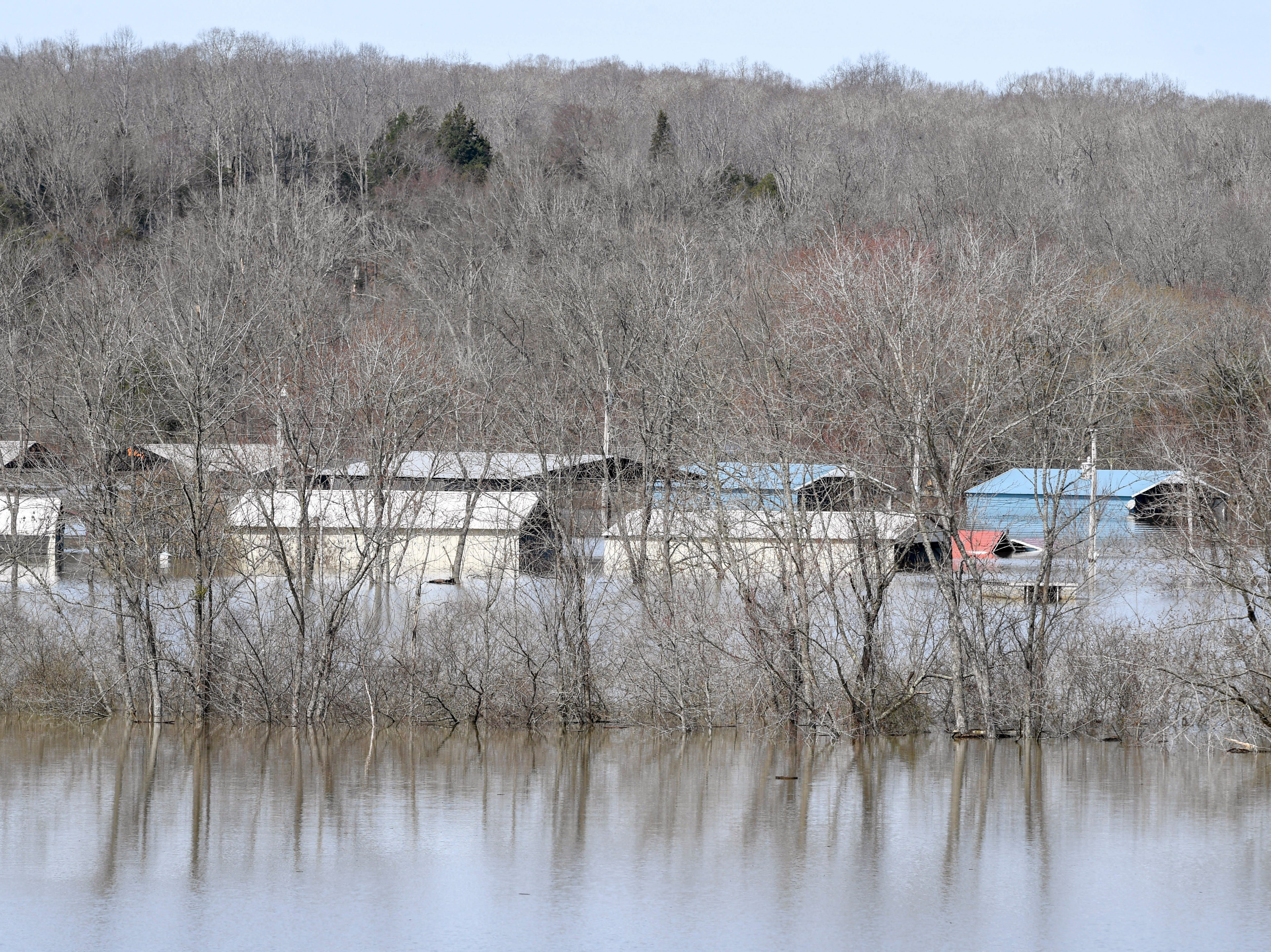 Homes, warehouses, and docks can be seen nearly overcome by flood waters at Lost Creek Boat Ramp, in Decaturville, Tenn., on Monday, Feb. 25, 2019.