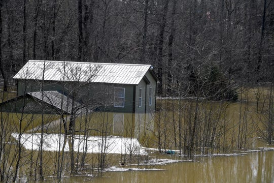 A to story home is submerged up to the top of it's first story at Nance Road, in Decaturville, Tenn., on Monday, Feb. 25, 2019.