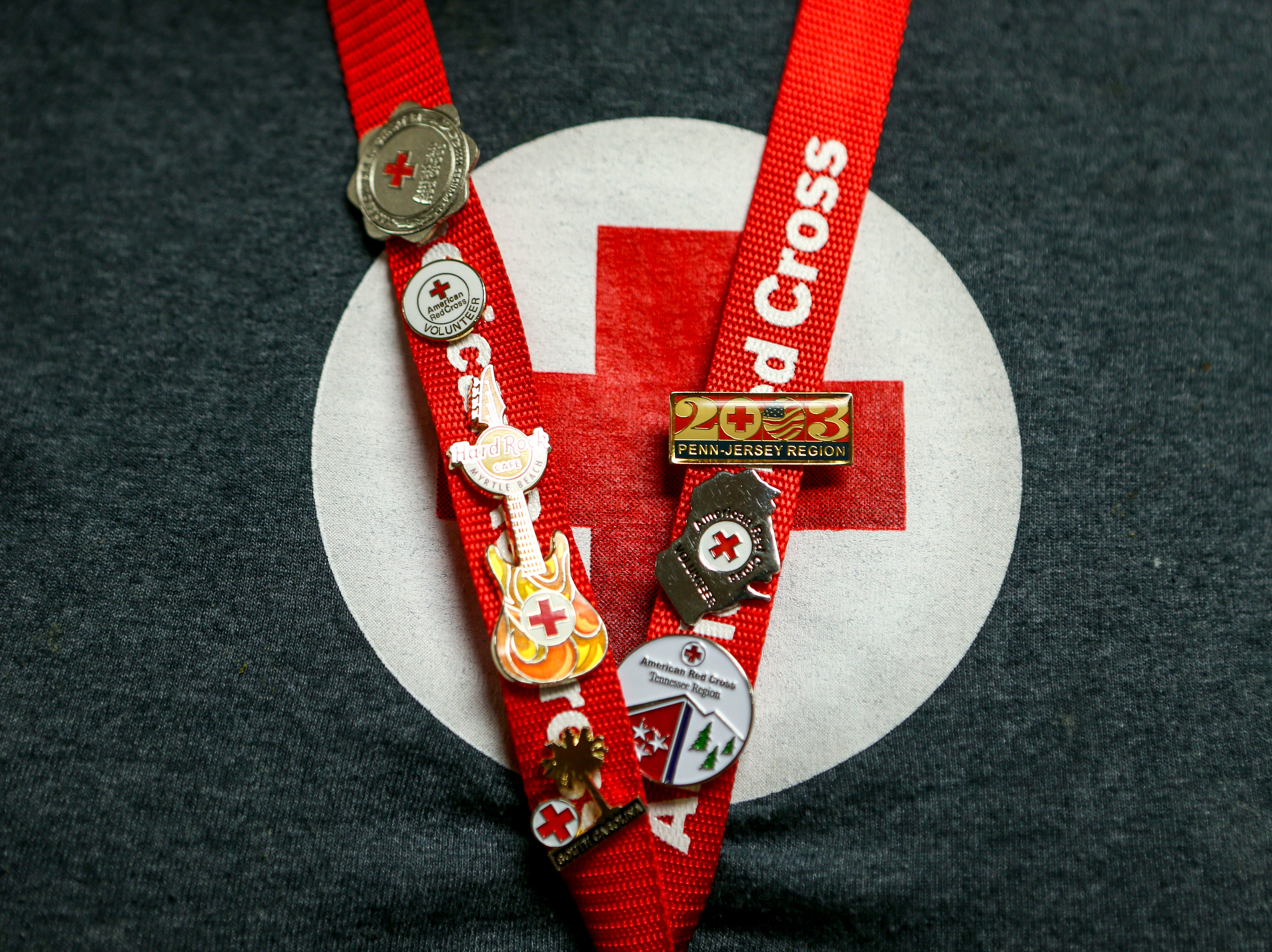 Shania Hart, the manager of the Red Cross shelter, wears her name tag with an assortment of pins she has collected at Savannah Church of Christ, in Savannah, Tenn., on Monday, Feb. 25, 2019.