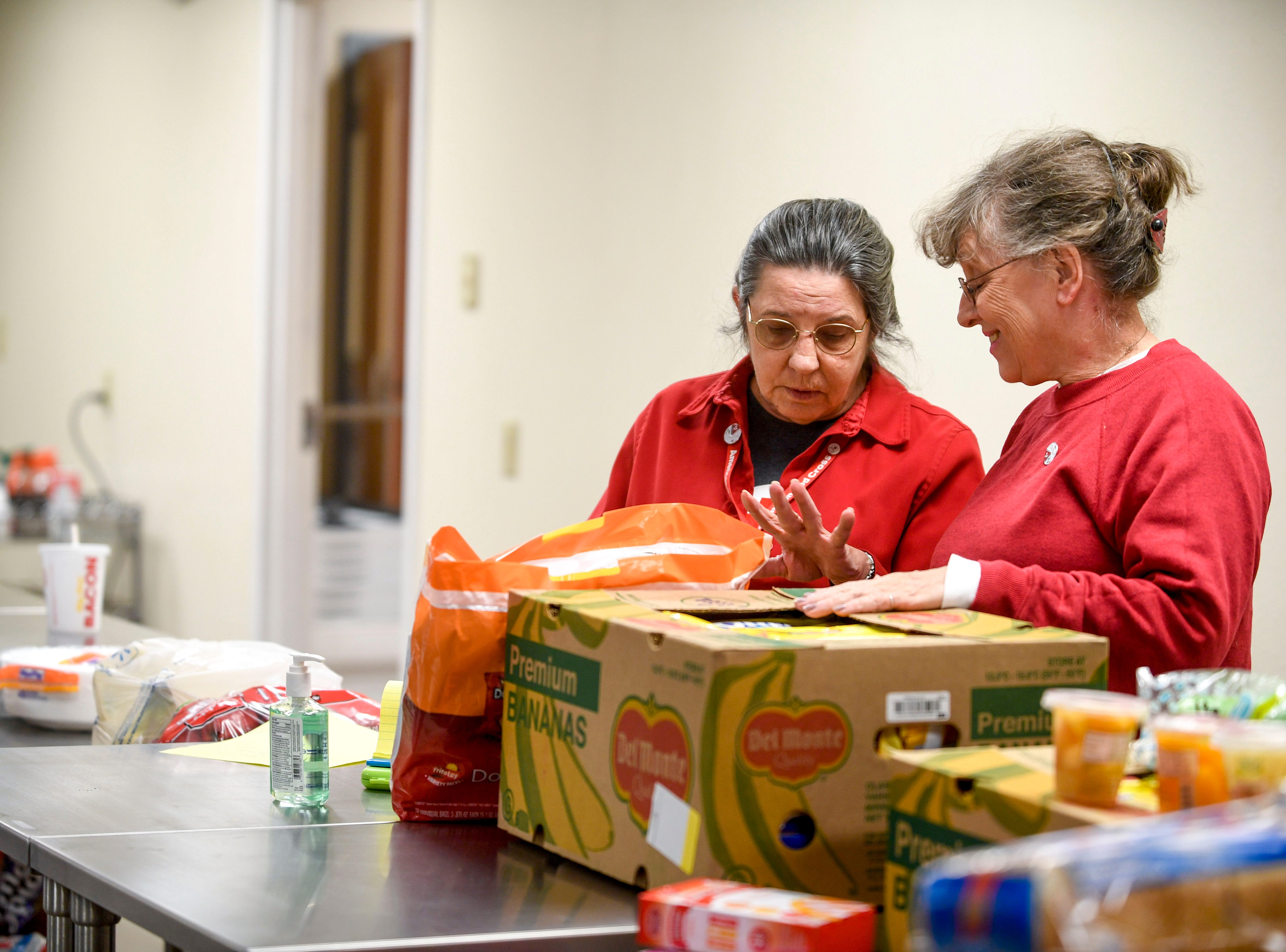 Lenora McMeekin, left, and Jackie, both volunteers with the Red Cross, take stock and make plans for use of supplies in the Red Cross station at Savannah Church of Christ, in Savannah, Tenn., on Monday, Feb. 25, 2019.