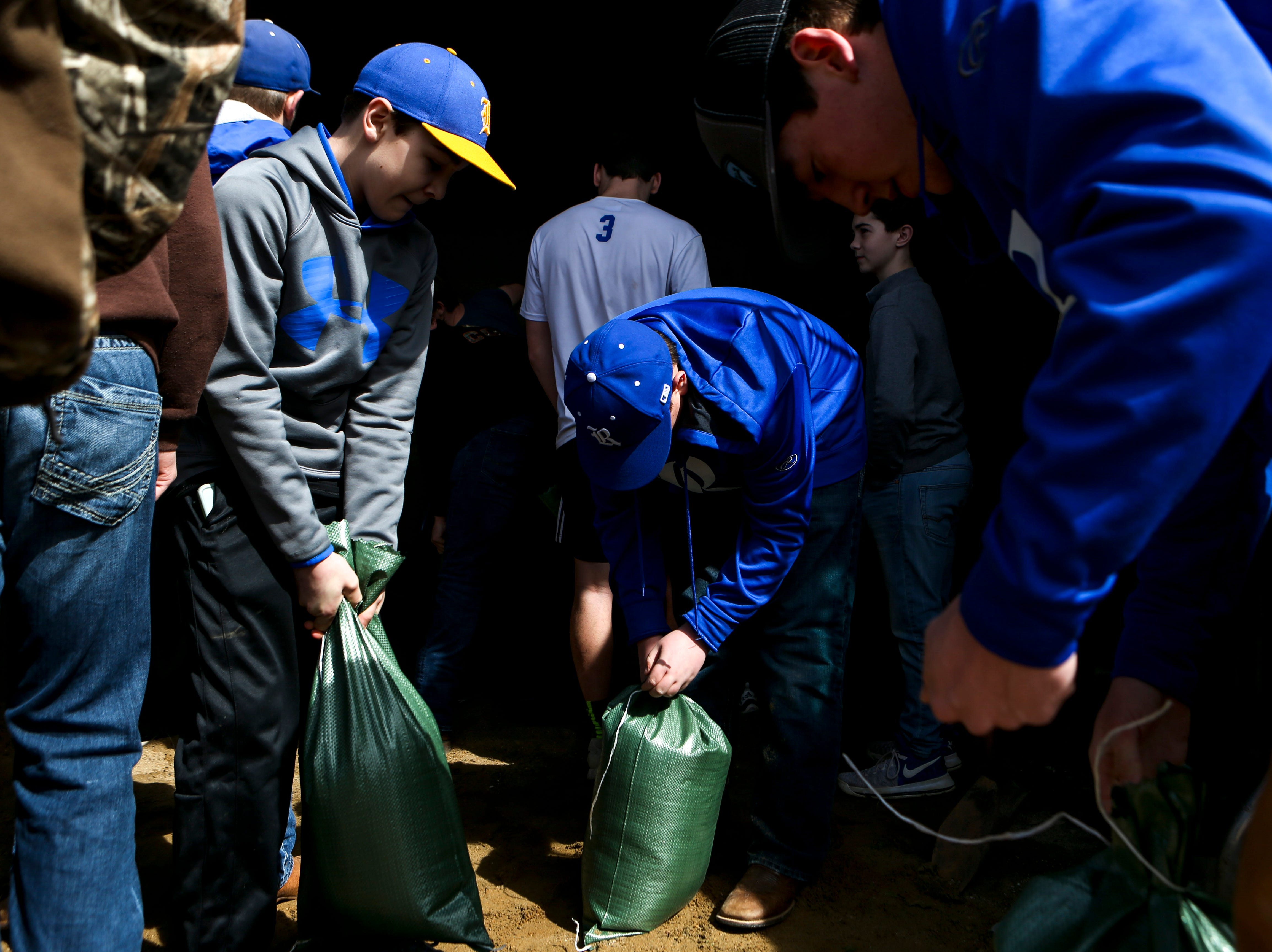 Riverside High School football and baseball players fill up and prepare sand bags for any residents that need to use them at Decatur County Highway Department, in Decaturville, Tenn., on Monday, Feb. 25, 2019.
