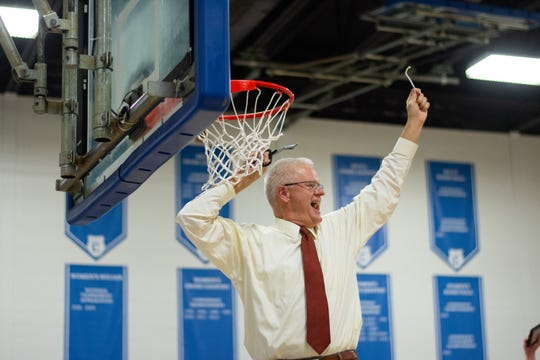 Maryville College men's basketball coach Randy Lambert celebrates a USA South Athletic Conference Tournament title by cutting a piece of the net following a 79-67 victory over Methodist on Feb. 23, 2019 in  Lookout Mountain, Ga.