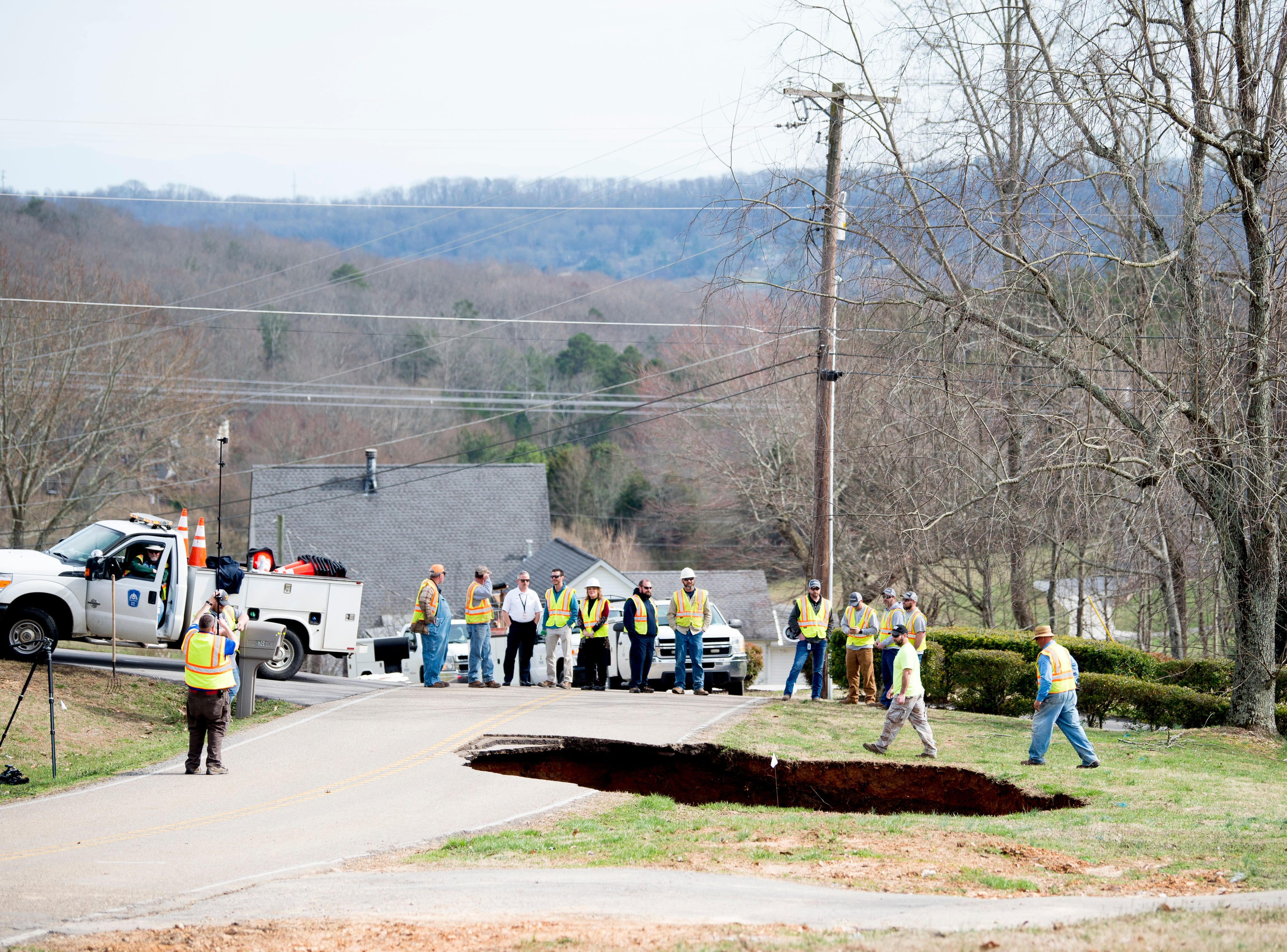 Workers from Hallsdale-Powell Utility District at the scene of a large sinkhole on Greenwell Road in Powell, Tennessee on Tuesday, February 26, 2019. The sinkhole is estimated to be around 20 feet deep.