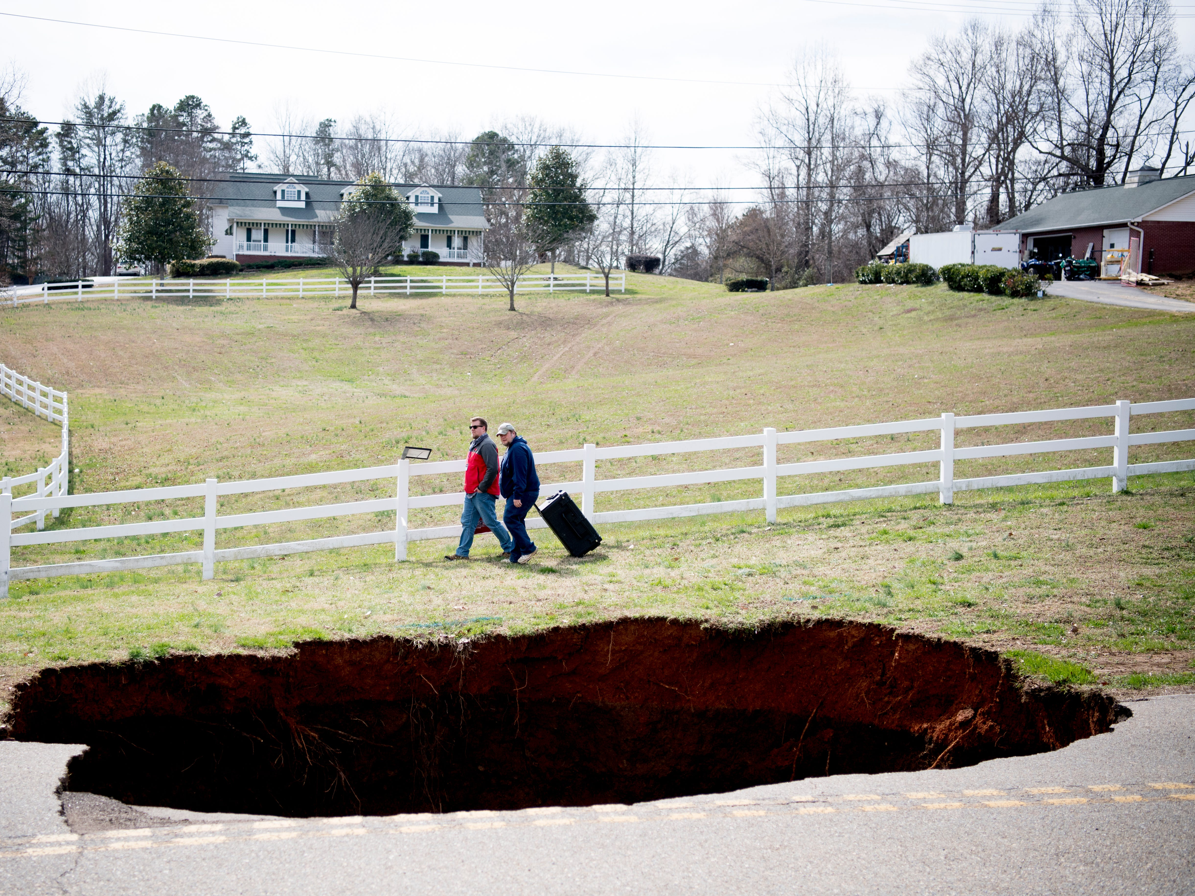 People walk past a large sinkhole on Greenwell Road in Powell, Tennessee on Tuesday, February 26, 2019. The sinkhole is estimated to be around 20 feet deep.