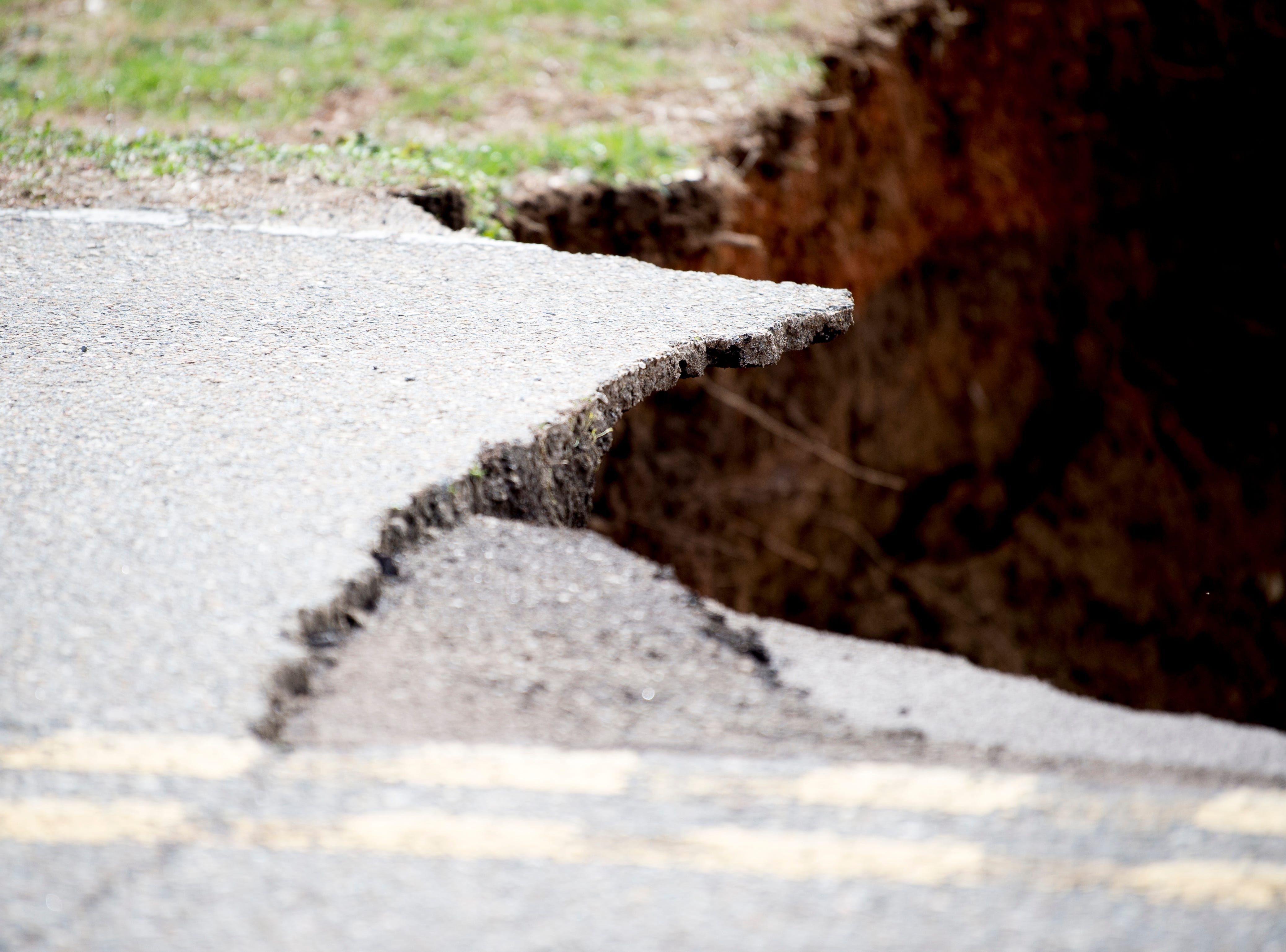 A chunk of the road can be seen swallowed up by a large sinkhole on Greenwell Road in Powell, Tennessee on Tuesday, February 26, 2019. The sinkhole is estimated to be around 20 feet deep.