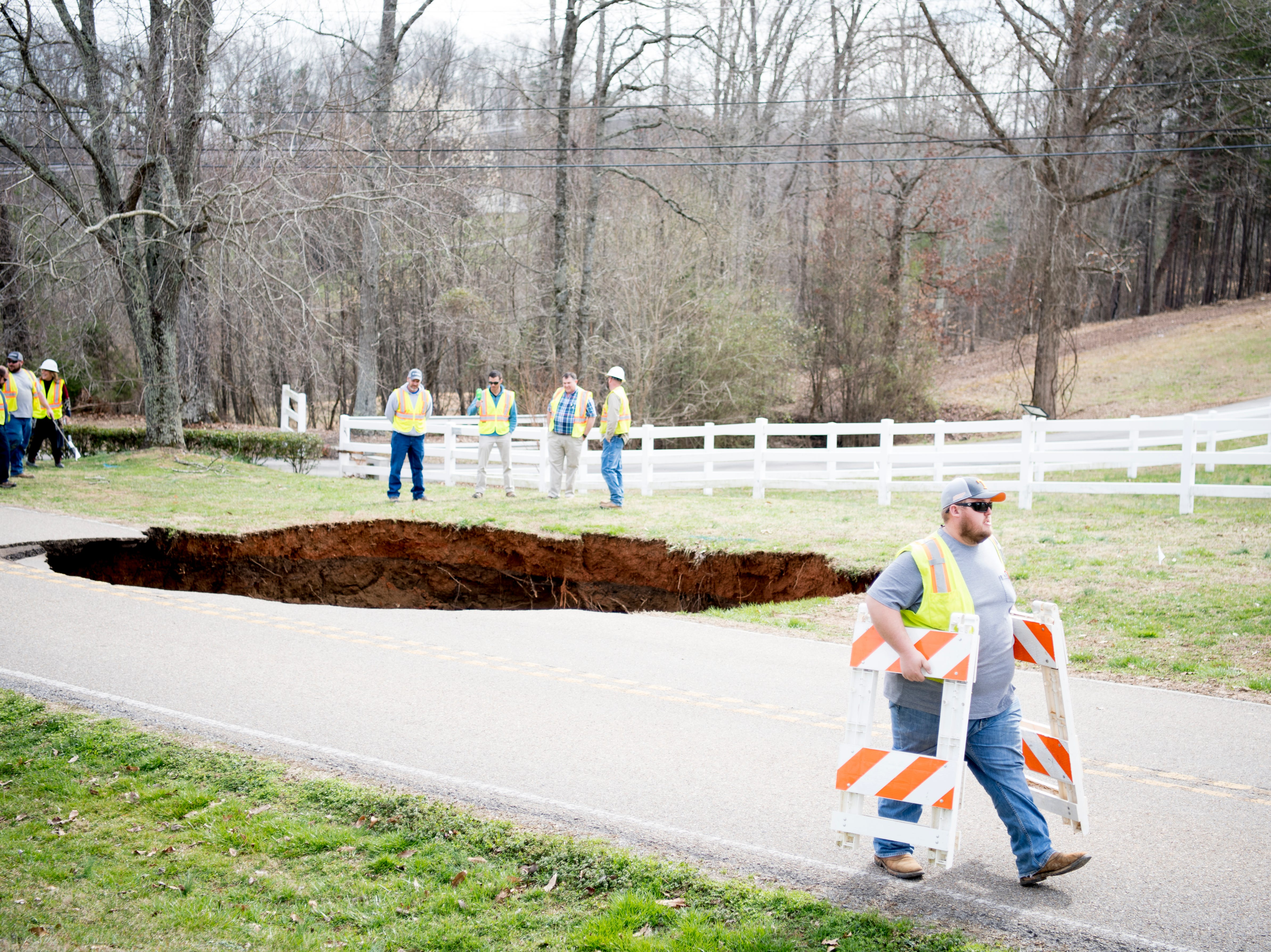 Workers close the road at the scene of a large sinkhole on Greenwell Road in Powell, Tennessee on Tuesday, February 26, 2019. The sinkhole is estimated to be around 20 feet deep.