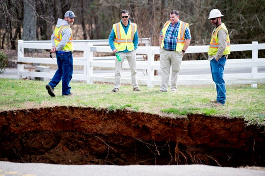 Workers from Hallsdale-Powell Utility District get a better view at the scene of a large sinkhole on Greenwell Road in Powell, Tennessee on Tuesday, February 26, 2019. The sinkhole is estimated to be around 20 feet deep.