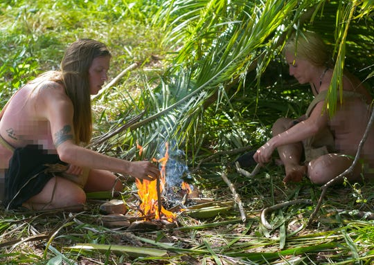 "Maryville's Sara Burkett, right, tends a fire with her survival partner Kate Wentworth on an episode of Discovery Channel's ""Naked and Afraid."""