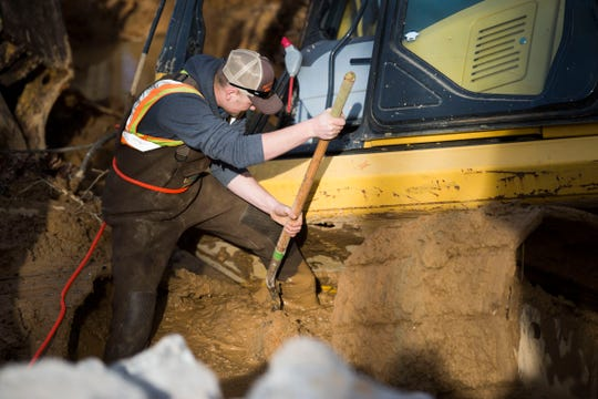 Knox County Highway Department employee Ryan Hatcher works to free a backhoe which got stuck in the mud while attempting to repair Everett Road in West Knoxville Monday, Feb. 25, 2019. A combination of the weekend's rain and an underground stream, caused a portion of the road to break away.