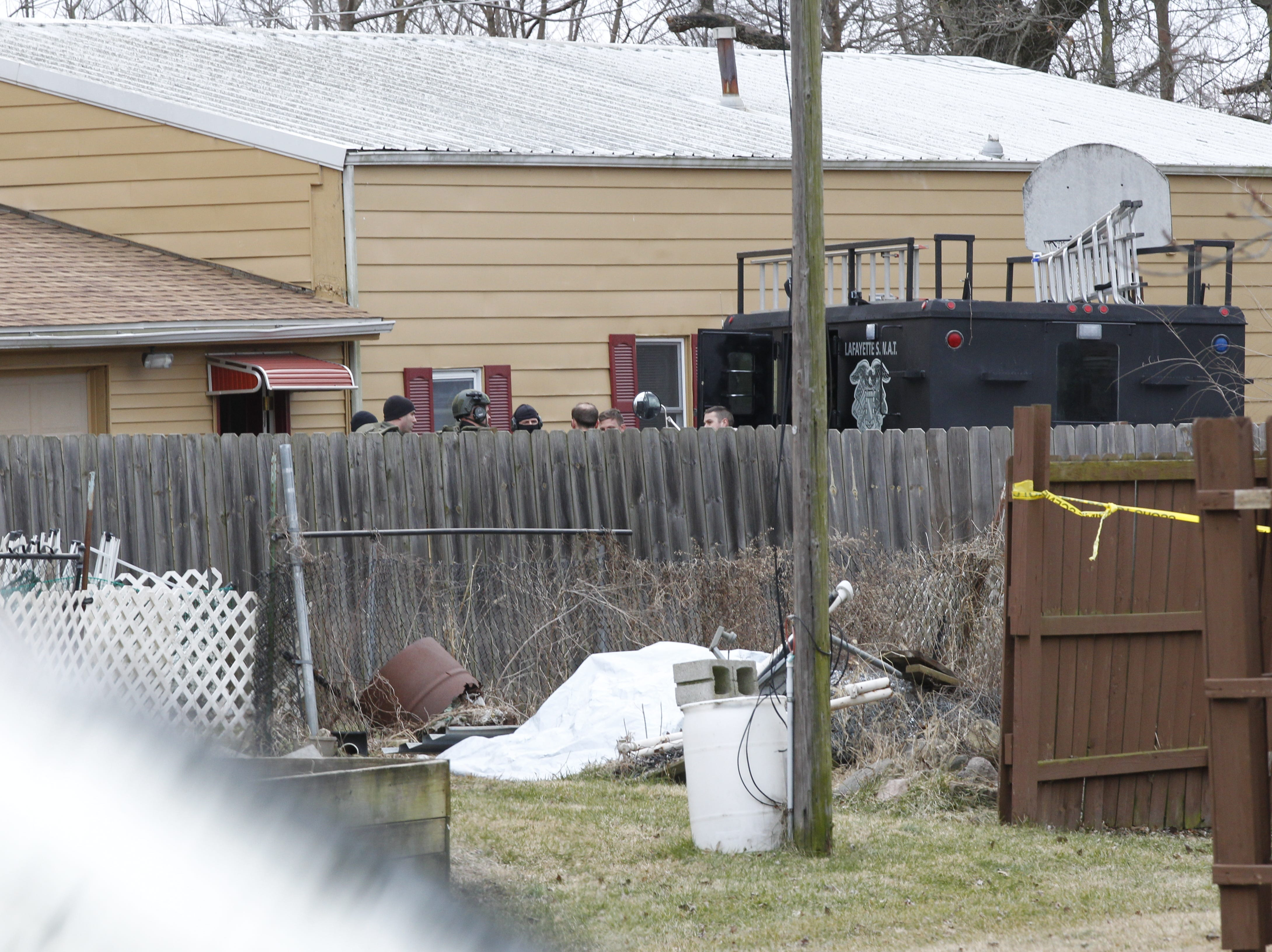 Lafayette police, including members of the SWAT team, converged in the 2500 block of Derbyshire Court Monday afternoon after Dustin Borders barricaded himself inside a house.