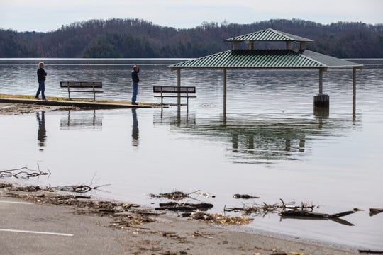 Visitors inspect the high waters around a flooded pavillion on Lake Cumberland just off from the Wolf Creek Dam in Jamestown, Kentucky on Tuesday. Feb. 26, 2019