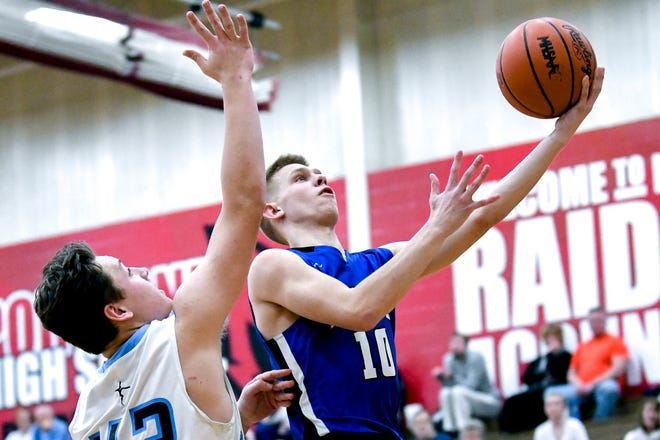 Ionia's Nick Szymanski, right, scores as Lansing Catholic's Charlie Nylander defends during the third quarter on Monday, Feb. 25, 2019, at Portland High School.
