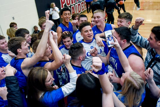 Ionia's basketball team and fans celebrate after defeating Lansing Catholic 66-64 on Monday, Feb. 25, 2019, at Portland High School.