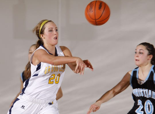 Grand Ledge's Lindsay Orwat, left, passes away from pressure by Grand Rapids Christian's Hayley Reitsma Tuesday, March 11, 2014, in DeWitt, Mich. Grand Ledge won 62-52.