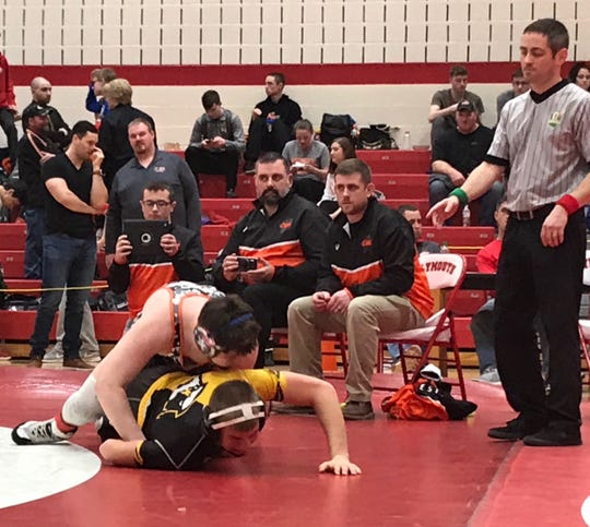 Unable to wrestle as he recovers from knee surgery, Sam Krupa shoots video of a teammate alongside assistant coach Eric Teague and head coach Cory Runkle.